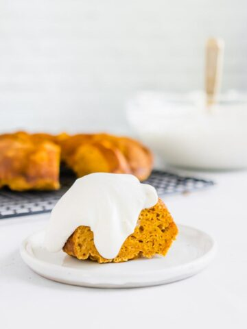 pumpkin bundt cake with cream cheese whipped cream on top on a white plate