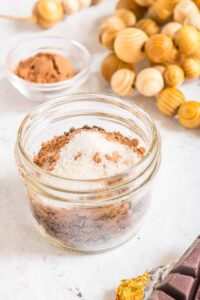 3 ingredient dark hot chocolate mix in glass jar with more ingredients in background