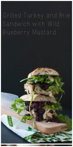 Grilled Turkey and Brie Sandwich with Wild Blueberry Mustard on a cutting board
