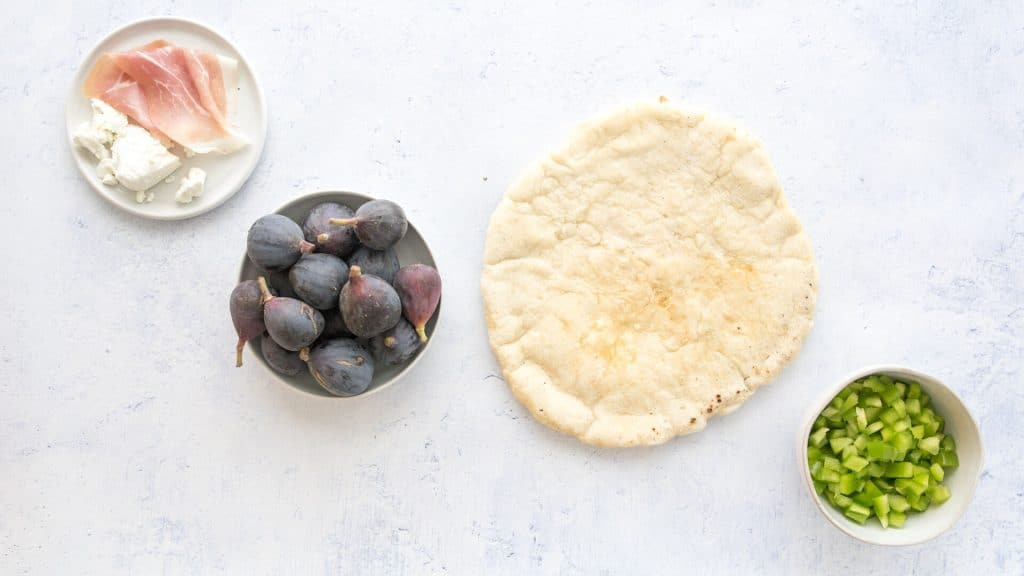 ingredients for fig and prosciutto pizza on a table