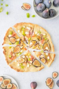 sliced fig and prosciutto pizza with fresh figs and peppers next to it