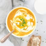 curry pumpkin soup with coconut milk in a white bowl with pumpkin and bread on the side