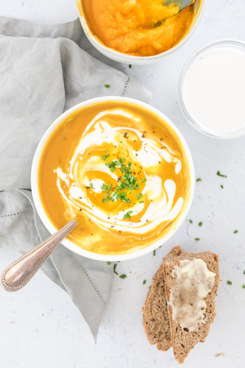 pumpkin soup with coconut milk swirled on top, in a white bowl with pumpkin and bread on the side