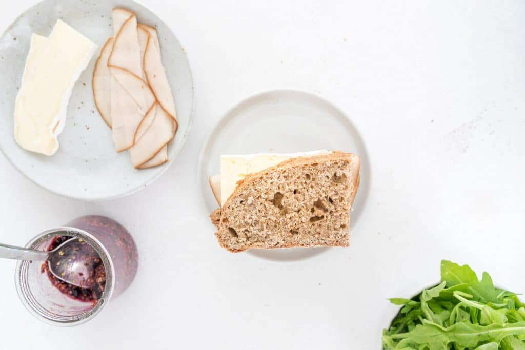 uncooked turkey and brie sandwich on a table with ingredients surrounding it