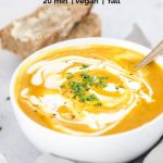 curry pumpkin soup with coconut milk swirl in a white bowl with bread in the background with text overlay