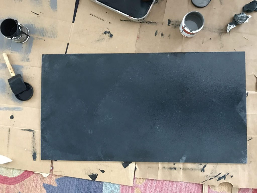 plywood painted black on the ground with paint materials