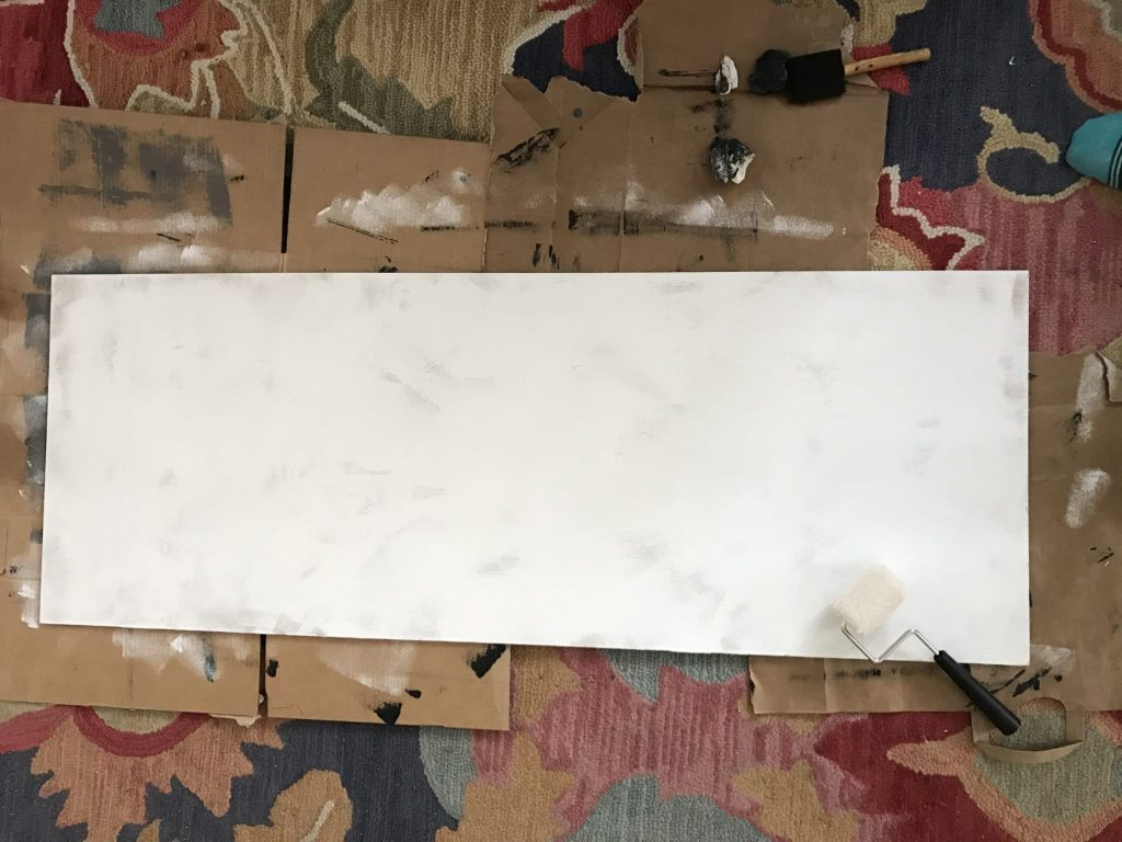 plywood painted white on carpet with cardboard under it