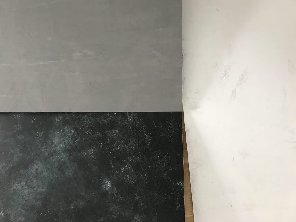 black, grey, and white painted plywood boards next to eachother