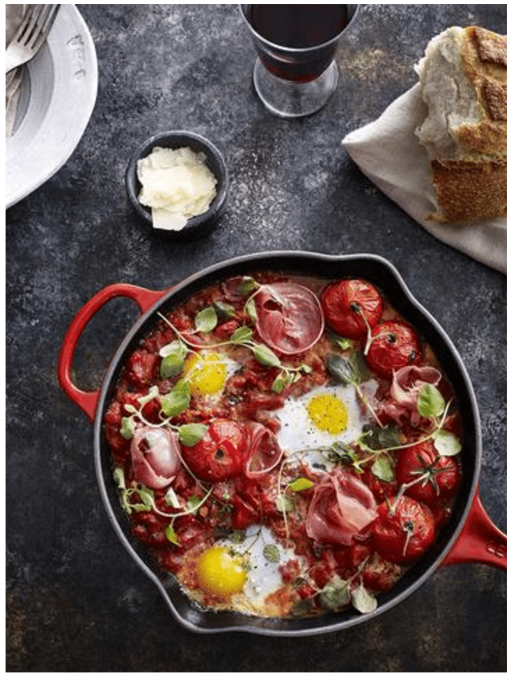 eggs and vegetables in a cast iron skillet with bread on the side