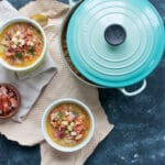 bean and bacon soup in bowls with a teal dutch oven