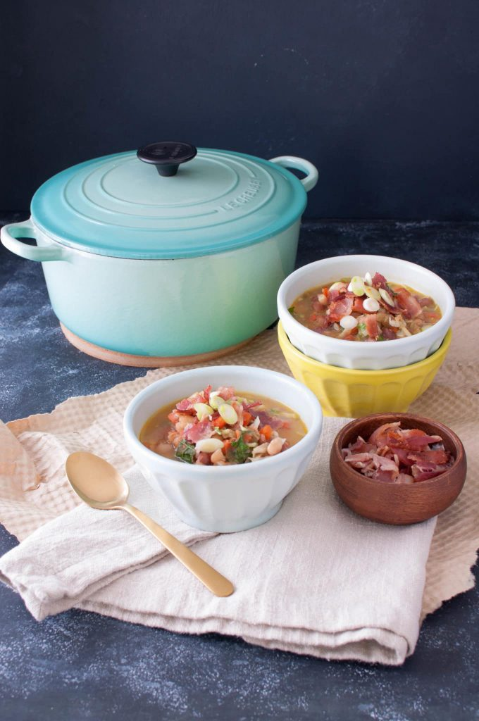 bean and bacon soup in bowls with large stock pot