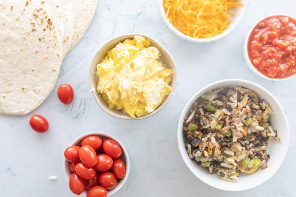 eggs, vegetables, tomatoes, and cheese for healthy breakfast tacos