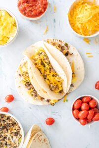 healthy breakfast tacos on a plate with ingredients surrounding them