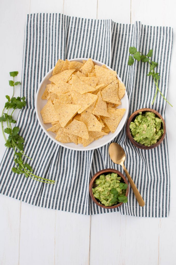 tortilla chips with guacamole in wooden bowls