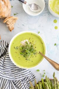 creamy asparagus soup in a white bowl with bread on the side