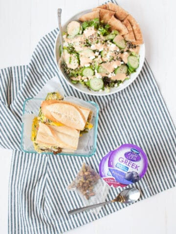 Dannon Light & Fit yogurt, sandwiches, and salad on a table