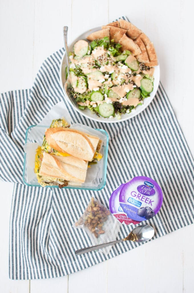 Dannon Light & Fit Greek yogurt, sandwich, and salad on a table