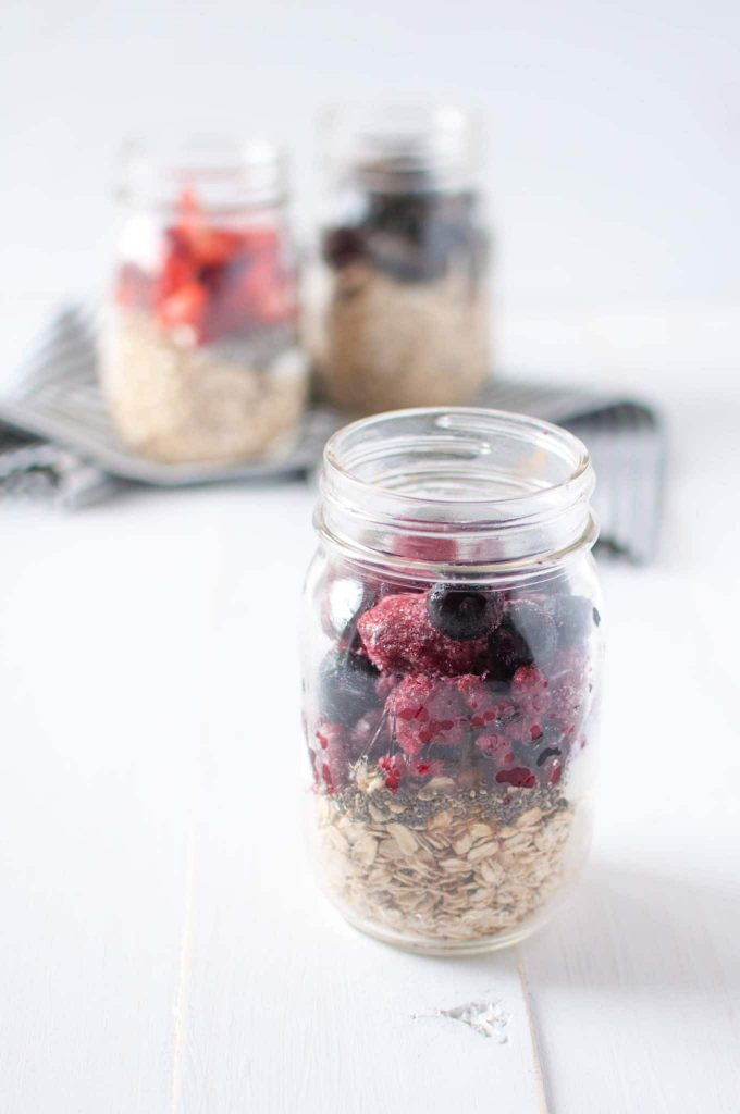 oatmeal and frozen berries in a glass jar with 2 jars of oatmeal in the background