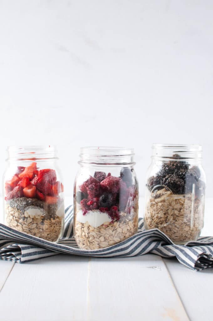 three glass mason jars in a row with oats, yogurt, and fruit on top