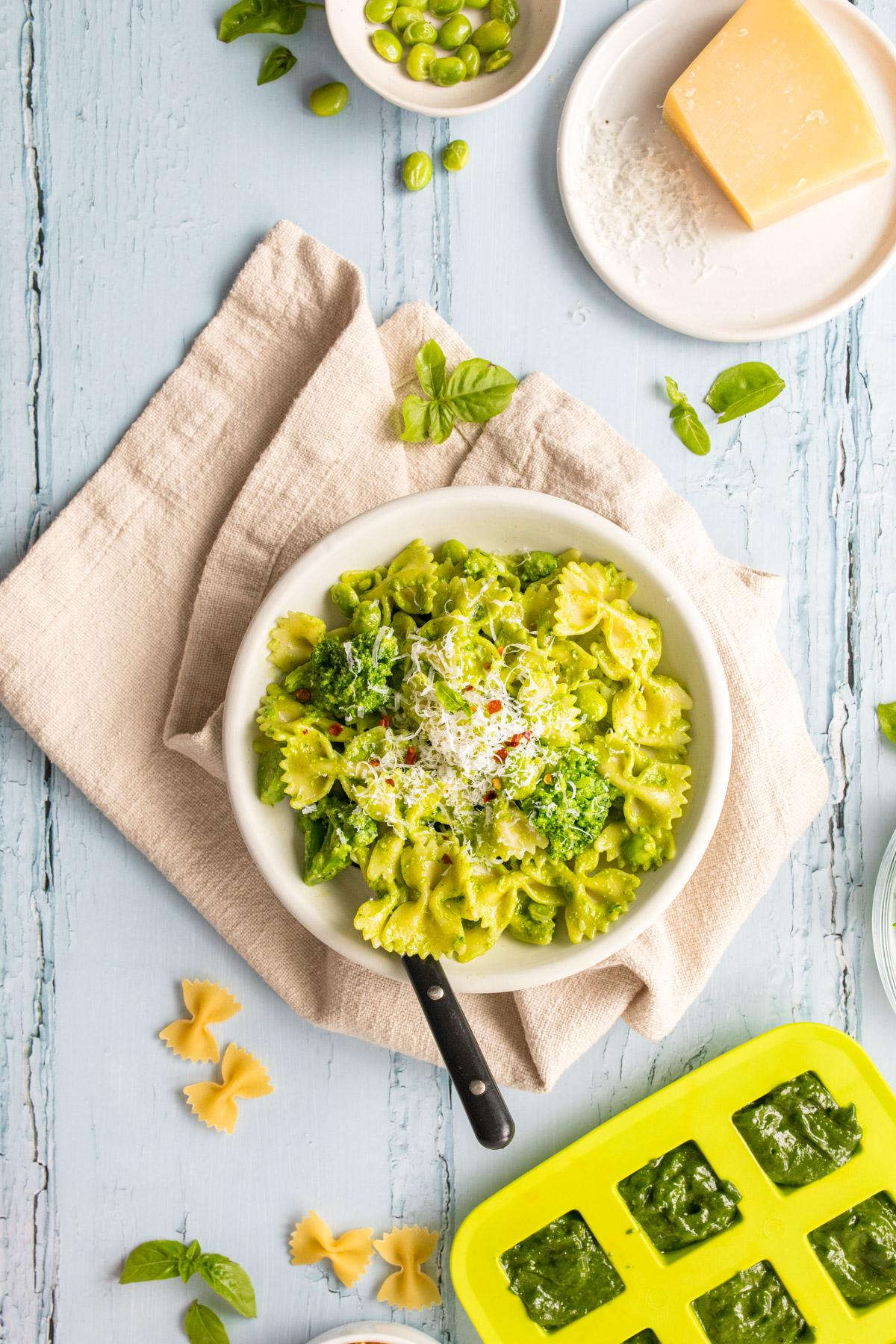 bowtie pasta with pesto in a white bowl with ingredients on table