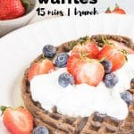 whole wheat mini chocolate waffles with cream and strawberries on table with text overlay