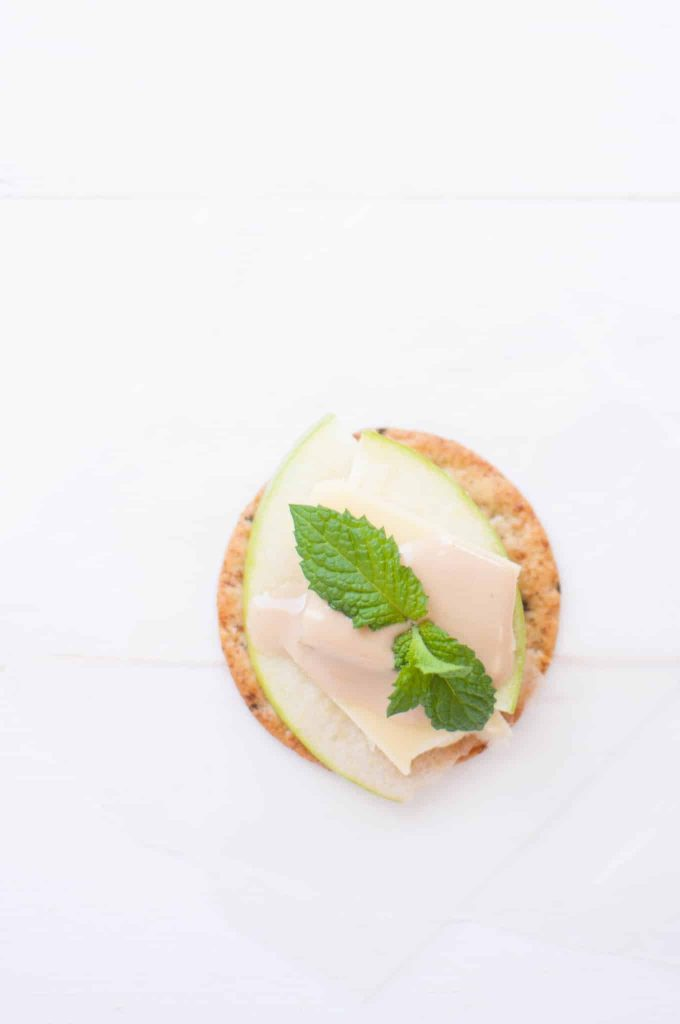 cracker with apples cheese and sauce with a mint sprig