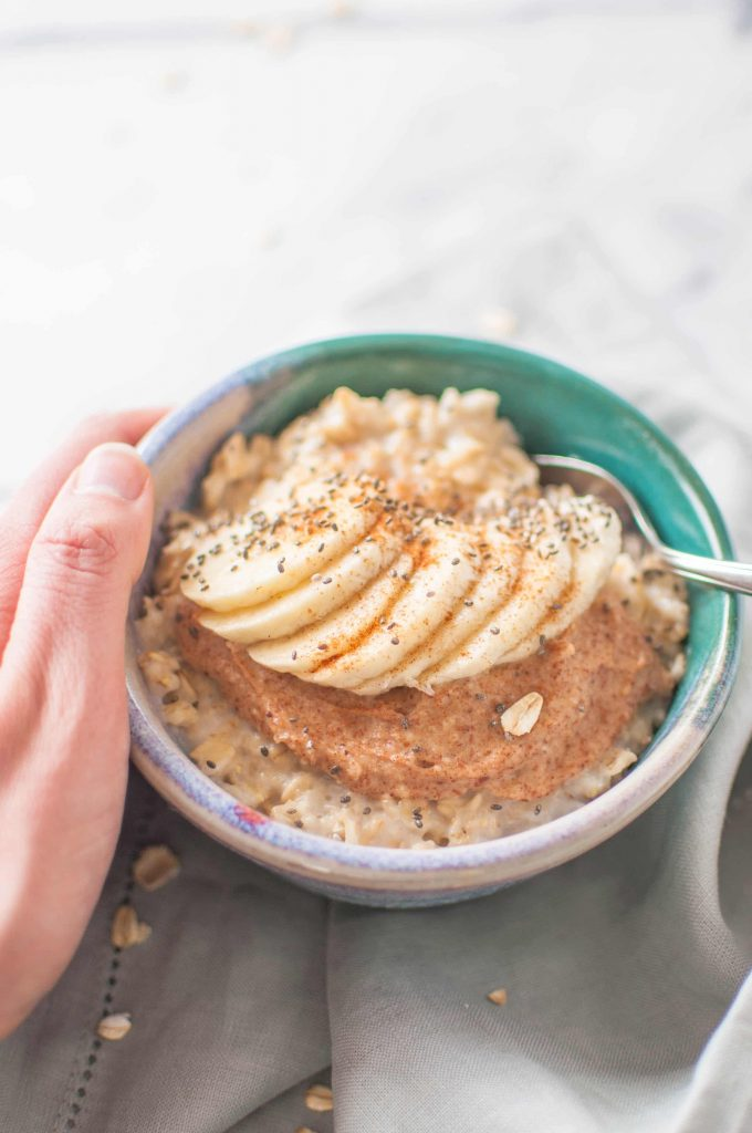 holding oatmeal with peanut butter and bananas on top