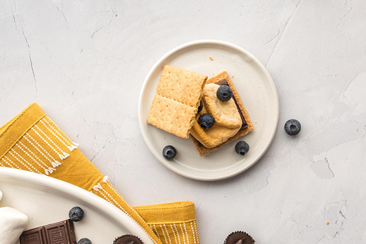smore with blueberries on a plate with ingredients and yellow towel next to it