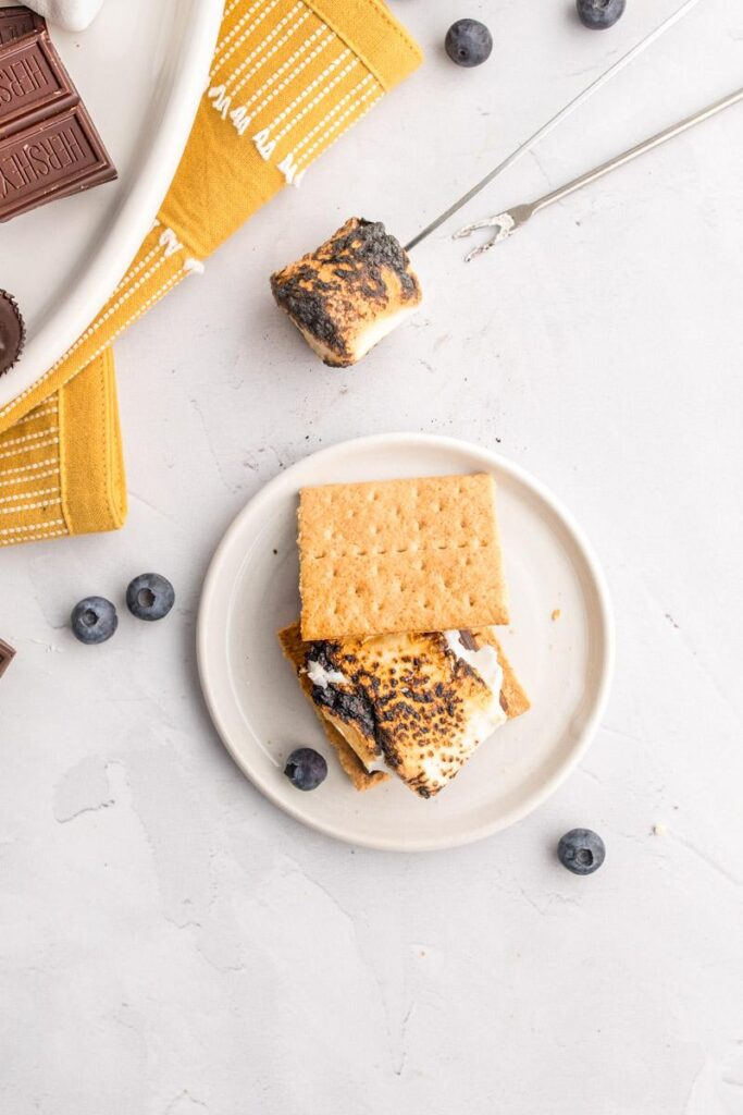 one smore on a table with ingredients around it