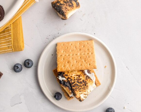 Stacked s'mores with toppings in the background