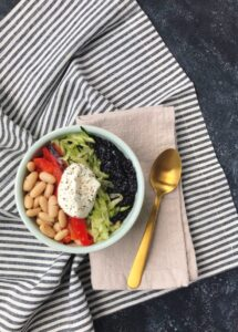 Black Rice and Cannellini Bean Buddha Bowl on striped towel with gold spoon