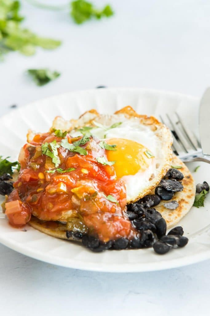 huevos rancheros with tomatoes on top