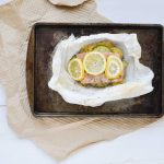 salmon with lemon slices in parchment paper on baking sheet