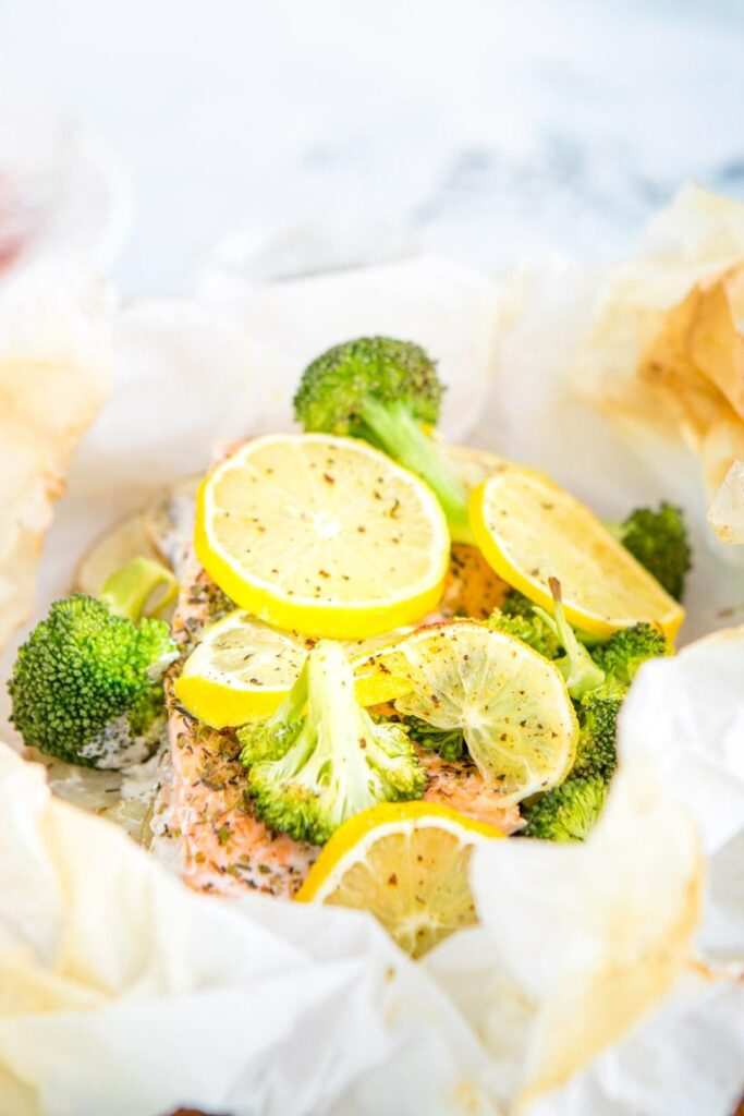 baked salmon, lemon slices, and broccoli in parchment paper