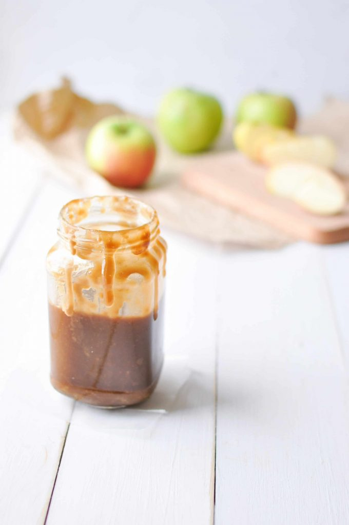 caramel sauce in a jar with apples in the background