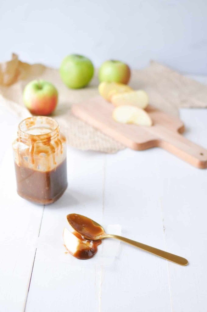 caramel sauce on spoon with caramel sauce in a jar and apples in the background