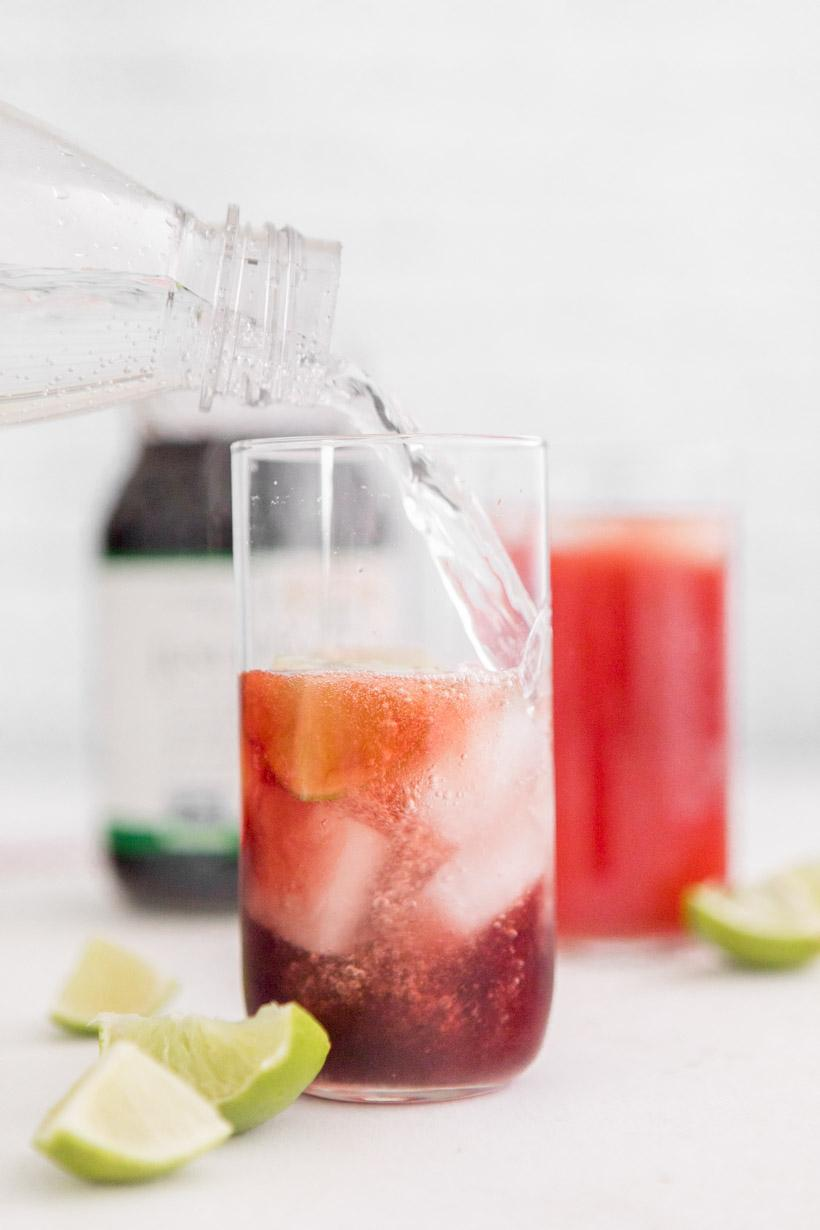 pouring sparkling water into pomegranate juice with ice