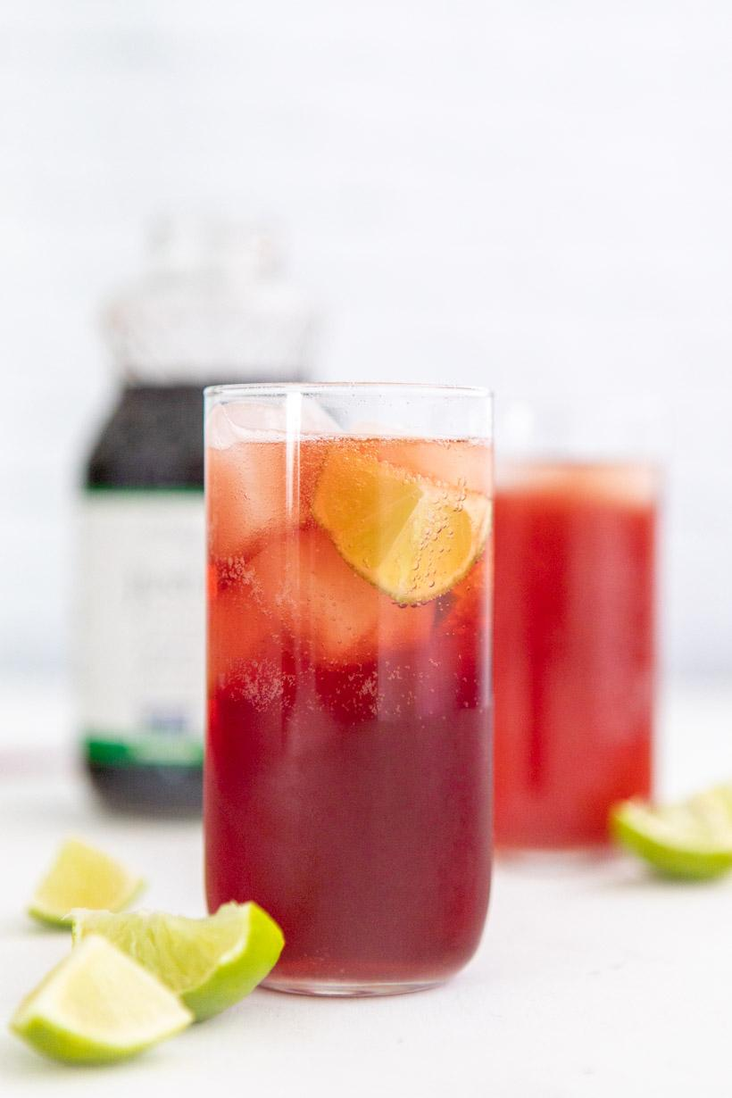 pomegranate lime spritzer in two glasses with ingredients in the background