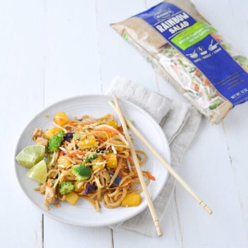 chicken noodle stir fry on white plate with bag of rainbow slaw