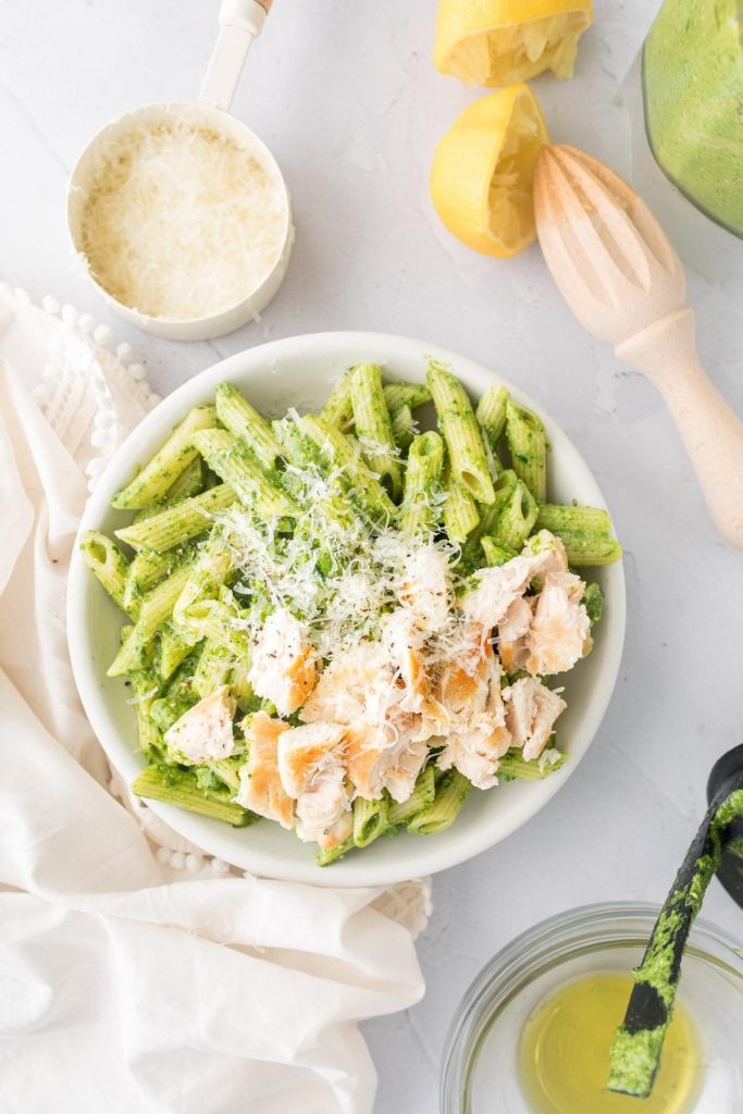 pistachio pasta with chicken on top with ingredients around it