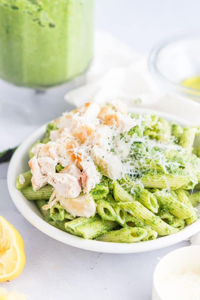 pistachio pasta with chicken and parmesan cheese in a white bowl