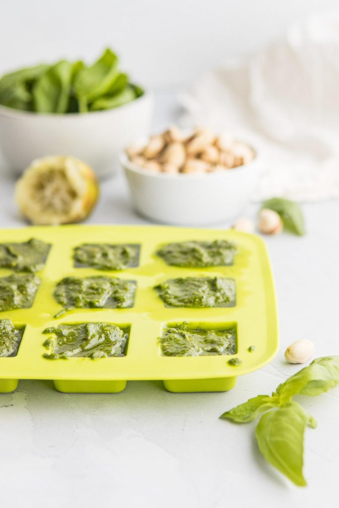 green ice tray with pistachio pesto in it and ingredients in background