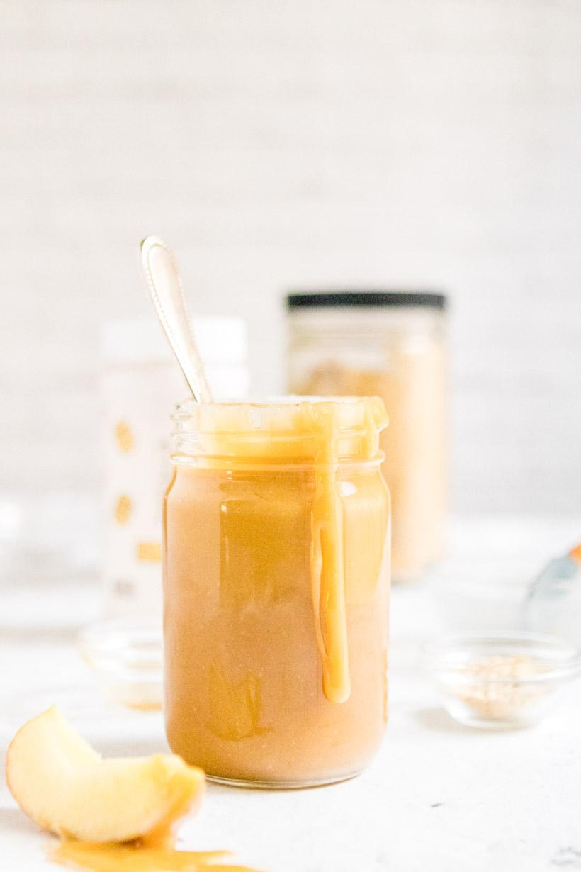 peanut butter caramel sauce on spoon with jar of caramel in background