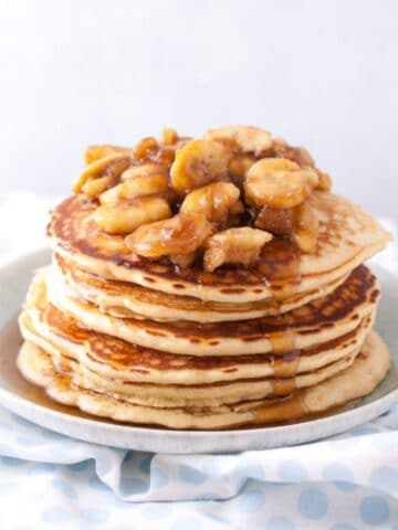 a stack of pancakes with sliced bananas and pecans on top