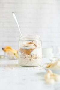 peanut butter overnight oats topped with banana in a glass jar with ingredients in the background