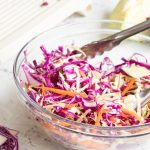red wine vinegar coleslaw in a glass bowl with tongs in it