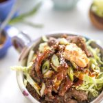 easy Korean beef bulgogi in a bowl with condiments in the background