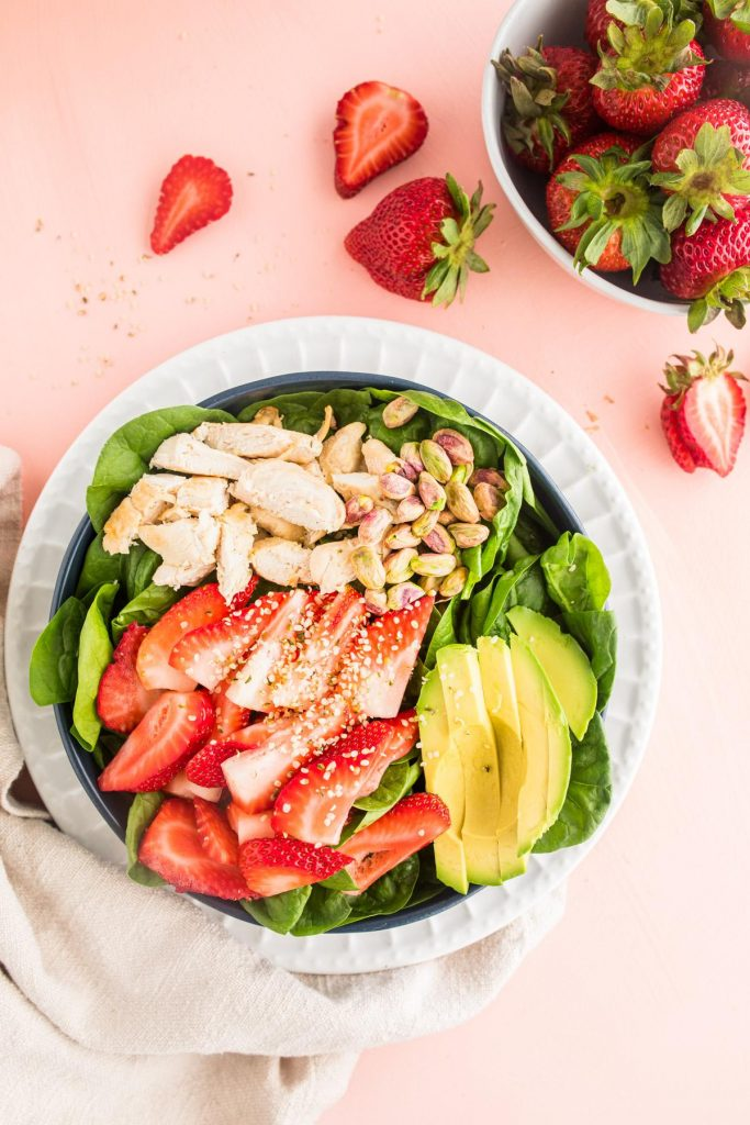 spinach strawberry salad in a blue bowl with strawberries next to it
