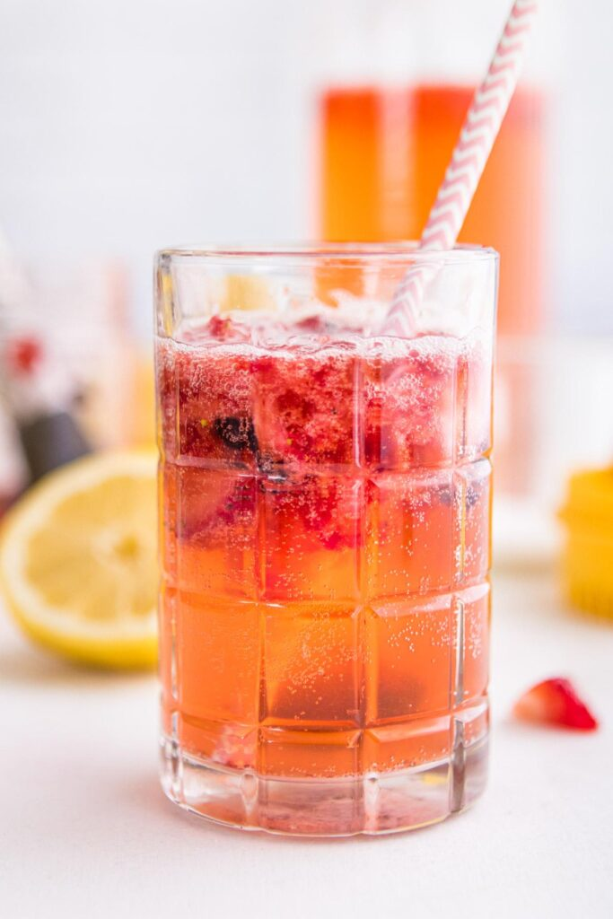 sparkling berry lemonade in a glass with ingredients behind it