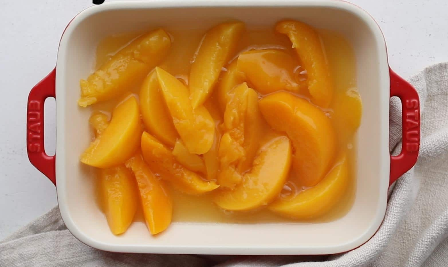 peaches in cast iron skillet ontop of a blue towel